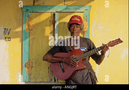 Man playing  acoustic guitar. Big Corn island Nicaraguan front of a bright yellow building near the beach - Stock Photo