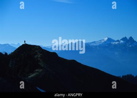 A lone hiker admiring the view near Elfin Lakes in Garibaldi Provincial Park, British Columbia, Canada. - Stock Photo