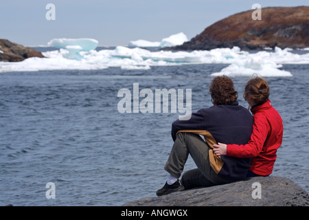 Man and woman iceberg watching from the shore in the town of Quirpon with pack ice in the harbour, Trails to the - Stock Photo
