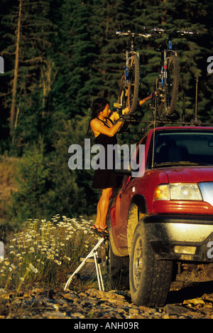 A young woman securing mountain bikes on the roof of the truck, Revelstoke, British Columbia, Canada. - Stock Photo
