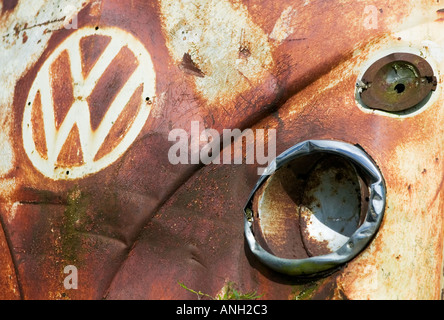 A close-up of the front section of an old, abandoned and rusting Volkswagen Transporter camper van - Stock Photo