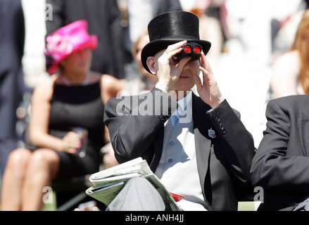 Man looking through binoculars at horse races in Epsom, Great Britain - Stock Photo