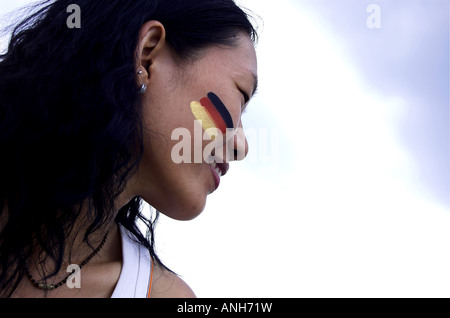 beautiful Chinese woman painting German flag on the face - Stock Photo