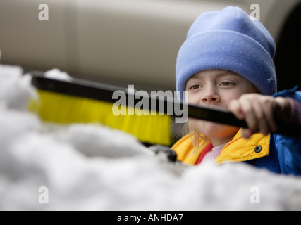Child removing snow from a car - Stock Photo