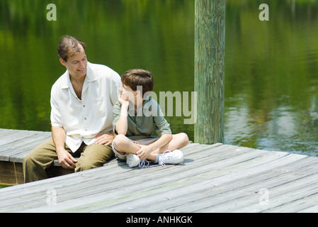Father and son sitting on dock, smiling at each other - Stock Photo