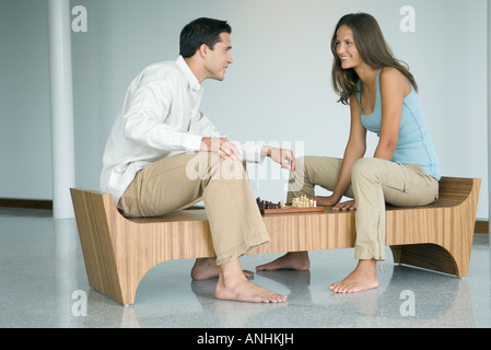 Young couple playing chess, smiling at each other - Stock Photo