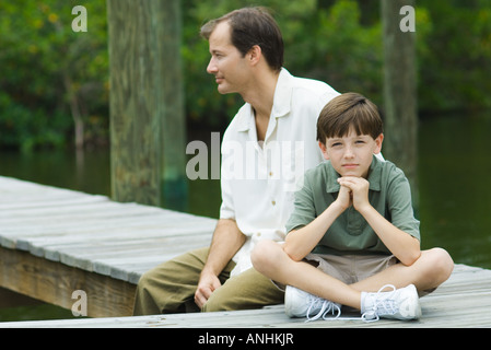Boy sitting on dock with father, smiling at camera - Stock Photo