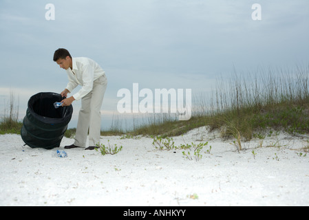 Man digging through trash can on beach, removing plastic bottles - Stock Photo