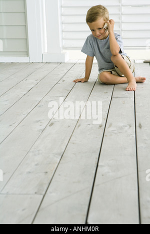 Boy sitting on deck listening to seashell - Stock Photo