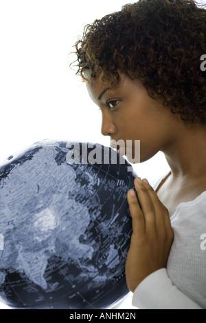 Young woman kissing globe, profile, close-up - Stock Photo