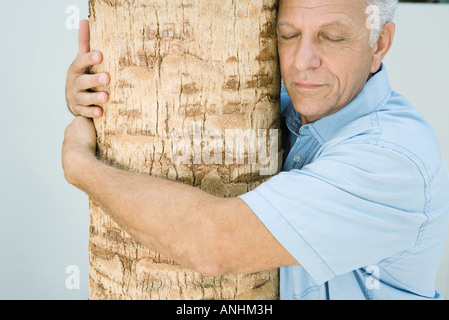 Mature man hugging tree trunk, eyes closed, smiling - Stock Photo