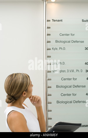 Woman looking at building directory, hand under chin - Stock Photo