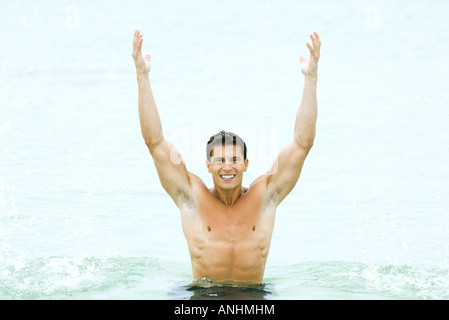 Muscular man standing in swimming pool with arms raised, smiling at camera - Stock Photo
