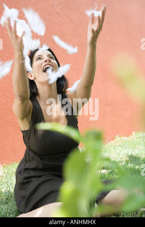 Woman sitting on the ground with arms raised to catch feathers, smiling - Stock Photo