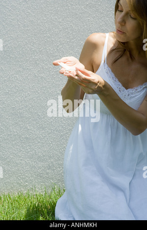 Woman in sundress holding butterfly in cupped hands - Stock Photo