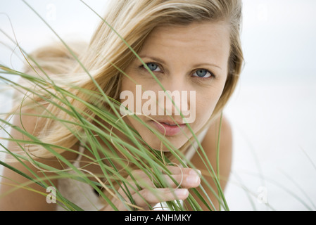 Woman looking at camera through tall grass, portrait - Stock Photo