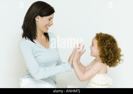 Woman and little girl playing clapping game, side view - Stock Photo