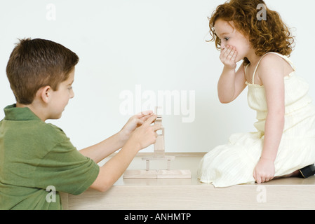 Boy stacking blocks while little sister watches, hand over mouth - Stock Photo