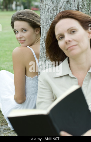 Woman and teen girl leaning against tree trunk, woman holding book - Stock Photo
