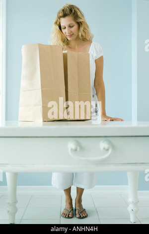 Woman looking into grocery bag - Stock Photo