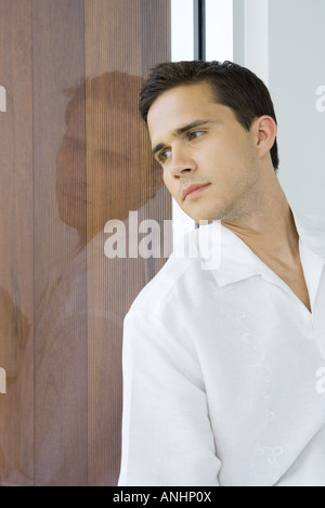 Young man leaning against window, looking out, close-up - Stock Photo