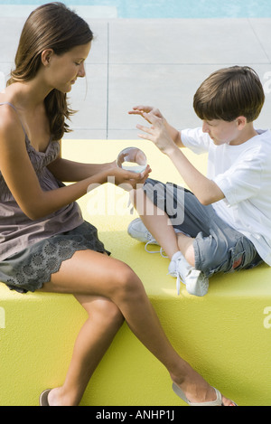 Teenage girl and younger brother sitting, looking at crystal ball together - Stock Photo