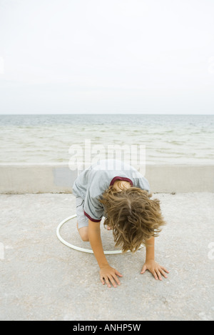 Boy crouching on all fours, playing with plastic hoop, head down - Stock Photo