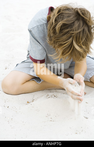 Boy sitting on the ground playing in sand, head down - Stock Photo