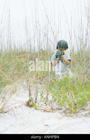 Boy crouching in tall grass, holding toy gun, looking at camera - Stock Photo