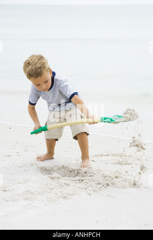 Young boy standing on beach, digging in sand with shovel, looking down - Stock Photo