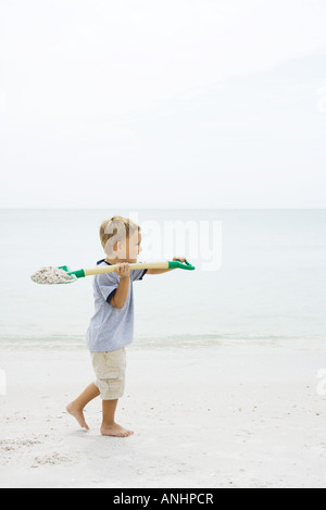 Boy walking on the beach, carrying shovel full of sand - Stock Photo
