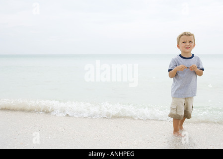 Boy at the beach, standing ankle deep in water, looking up and smiling - Stock Photo