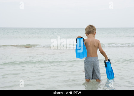 Young boy standing knee deep in water, carrying flippers, rear view - Stock Photo