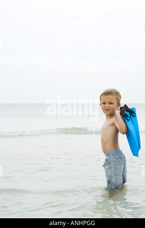 Young boy standing knee deep in water, carrying flippers, looking over shoulder at camera - Stock Photo
