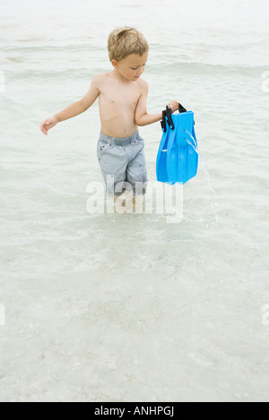 Young boy walking knee deep in water, carrying flippers, looking down - Stock Photo