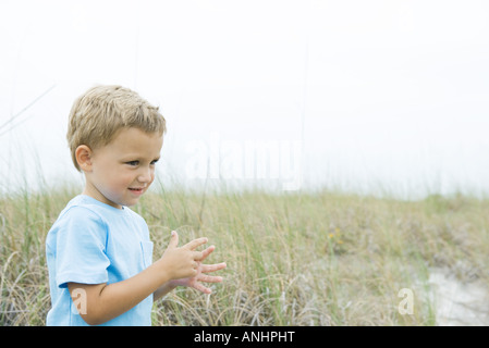 Young boy standing in tall grass, looking away, side view - Stock Photo