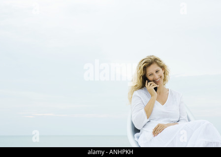 Woman sitting in chair outdoors, using cell phone, smiling - Stock Photo