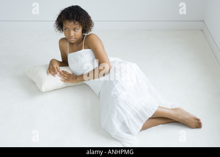 Young woman lying on cushion on the ground, looking away, full length - Stock Photo