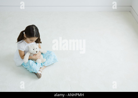 Girl sitting on the ground holding teddy bear on lap, high angle view - Stock Photo
