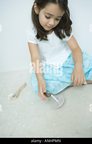 Girl sitting on the ground playing with top, close-up - Stock Photo