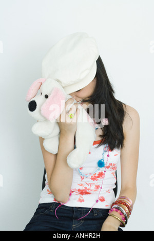 Teenage girl hiding face with stuffed toy, laughing - Stock Photo