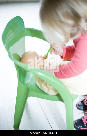 Blonde toddler girl pretending to feed baby doll - Stock Photo
