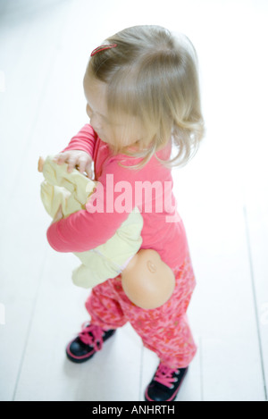 Blonde toddler girl holding baby doll upside down - Stock Photo