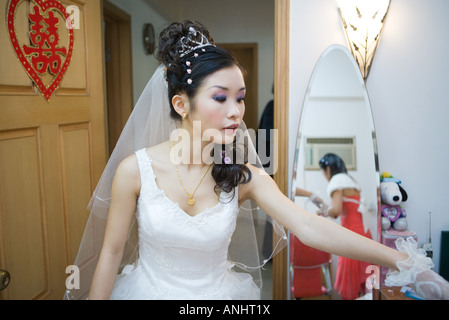 Bride in bedroom, Chinese character on door, looking away - Stock Photo