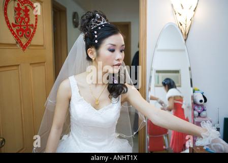 Bride in bedroom, Chinese character on door, looking away - Stock Photo