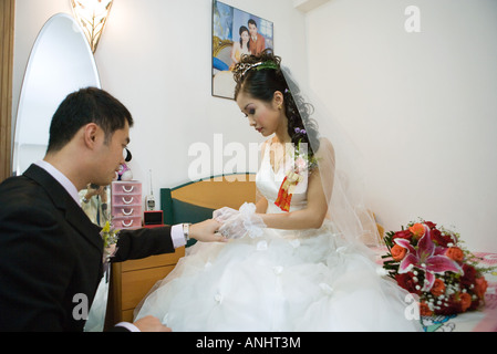 Bride and groom face to face in bedroom, holding hands - Stock Photo