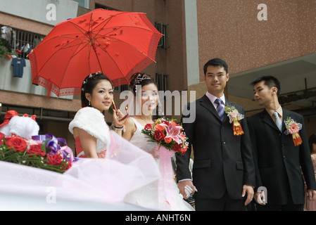 Chinese wedding, bride and groom standing with bridesmaid and best man - Stock Photo