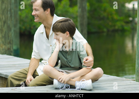 Man sitting on dock with arm around son's shoulder, both looking away and smiling - Stock Photo