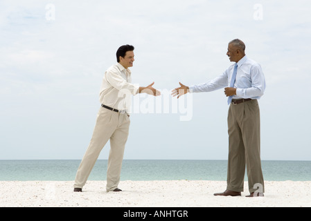 Two businessmen standing on the beach, reaching out to shake each other's hands - Stock Photo