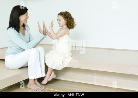Little girl playing clapping game with mother - Stock Photo